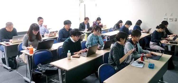 写真:勉強会参加者の写真。15,6名の参加者がスマホやPCを操作している