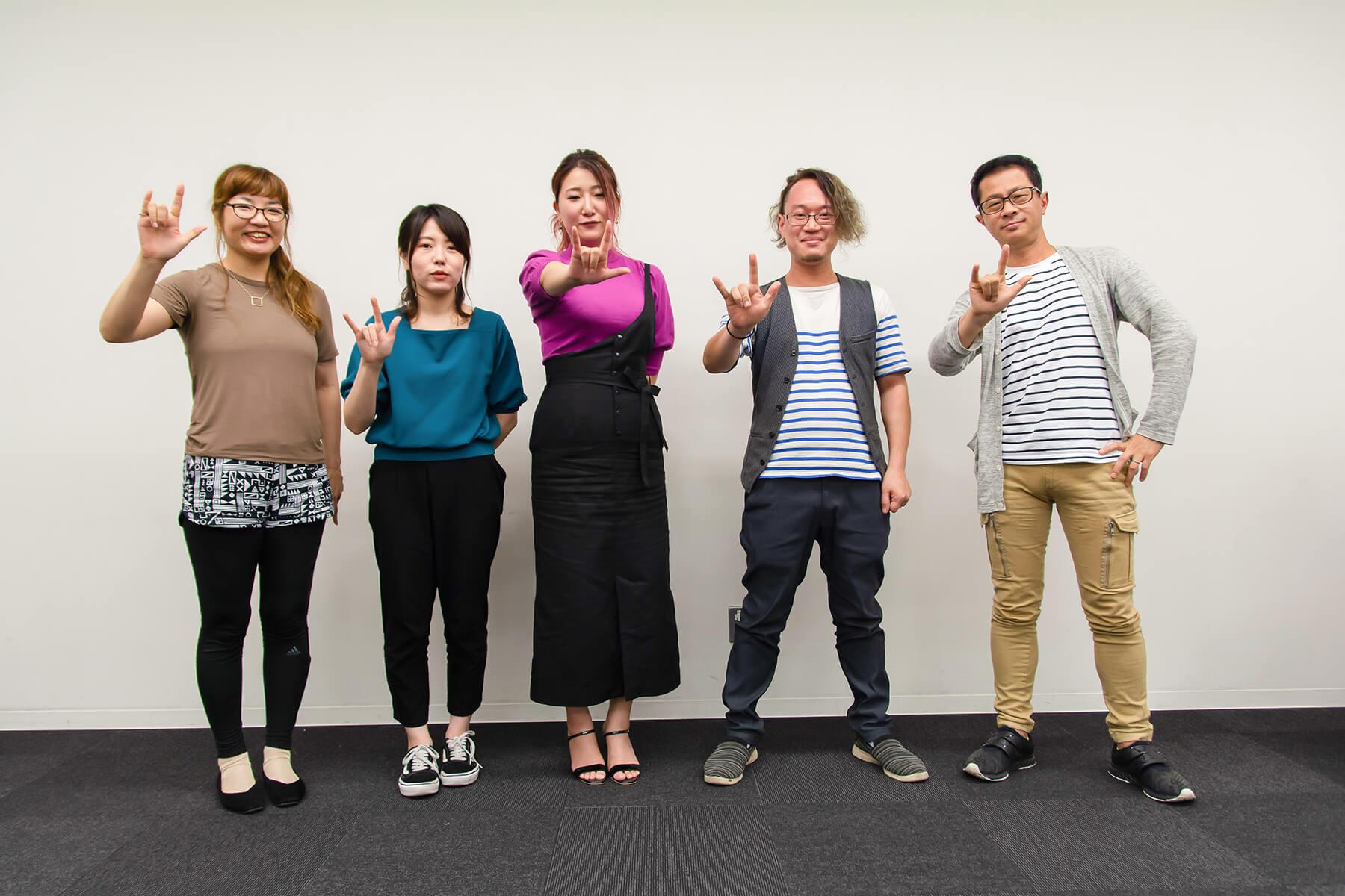 写真:登壇者皆さんの集合写真。全員右手を突き出し小指と人差し指を立てたポーズ